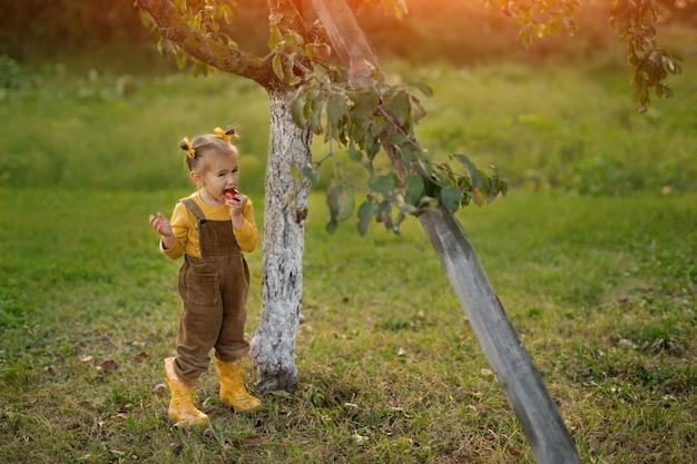 Ein mädchen isst einen roten reifen apfel unter einem apfelbaum in einem obstgarten