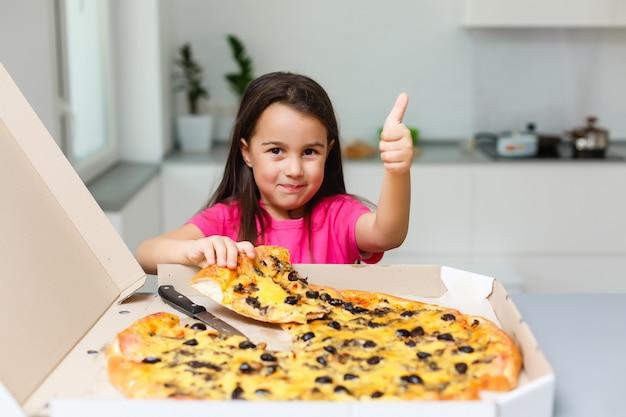 Ein mädchen isst zu hause pizza