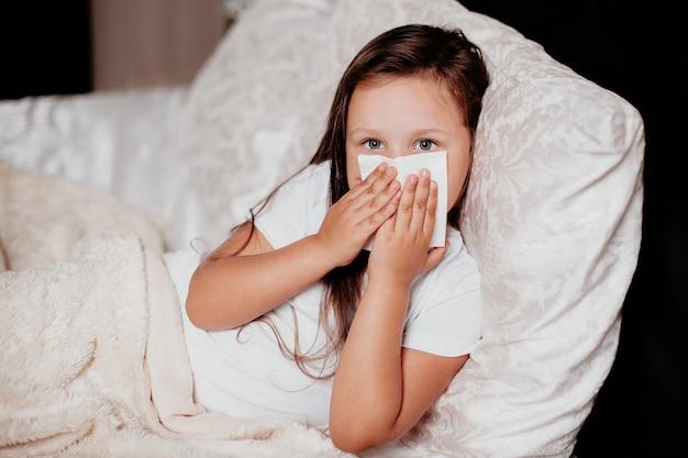 Ein mädchen liegt auf dem bett in einem schönen schlafzimmer, niest und bedeckt ihre nase mit einem taschentuch, der herbstkälte, der zweiten welle des virus