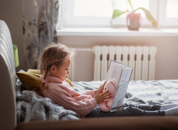 Ein mädchen liest ein buch in einem raum, der auf einem bett liegt