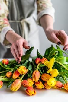Ein mädchen macht einen strauß aus gelben, orangefarbenen und roten tulpen