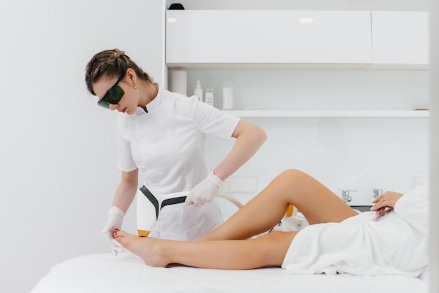 Ein mädchen macht laser-haarentfernung auf modernen geräten in einem spa-salon