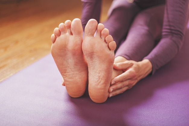 Ein mädchen macht yoga-asanas auf einem lila teppich im wohnzimmer.