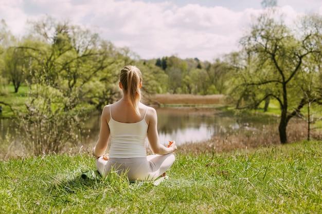 Ein mädchen meditiert in der lotus-position an der frischen luft im park.