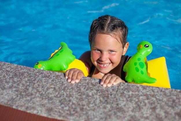 Ein mädchen mit armbinden, das in aufblasbaren armbinden schelmisch lächelt und sich am rand des pools festhält...