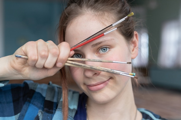 Ein mädchen mit blauen augen und roten haaren hält viele pinsel in der hand und schaut durch sie hindurch. frau bei dem zeichnen von ölgemälden.