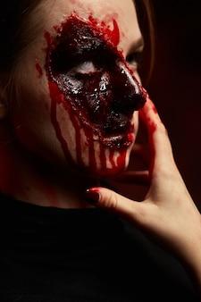 Ein mädchen mit blutigem make-up im gesicht für halloween auf violettem hintergrund