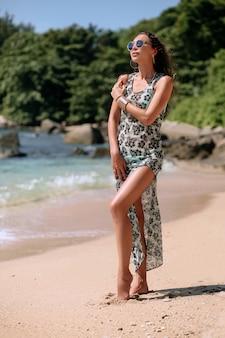 Ein mädchen mit braunen gewellten haaren in einem langen kleid und mit großen armbändern am arm ruht sich am strand aus. strandmode. freizeit und reisen