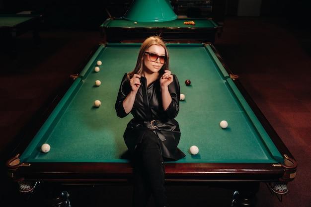 Ein mädchen mit brille sitzt auf einem billardtisch in einem club. russisches billard.