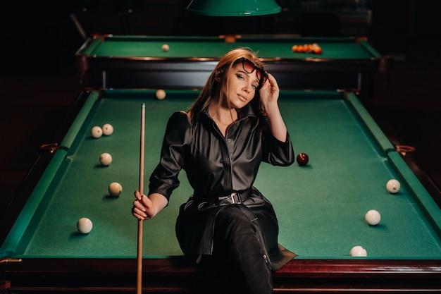 Ein mädchen mit brille sitzt auf einem billardtisch in einem club