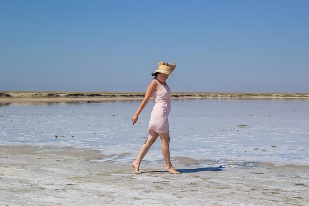 Ein mädchen mit dunklen haaren in einem rosa kleid und einem strohhut läuft an einem warmen, sonnigen tag barfuß am ufer eines salzsees entlang. sommerurlaub
