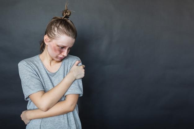 Ein mädchen mit einem blauen auge steht nach einem streit mit ihrem mann und ihrem freund an einer dunklen wand, umarmt sich und ist traurig. häusliche gewalt. aggression des mannes