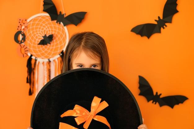 Ein mädchen mit einem bösartigen blick schaut in erwartung von halloween hinter einem großen hexenhut hervor