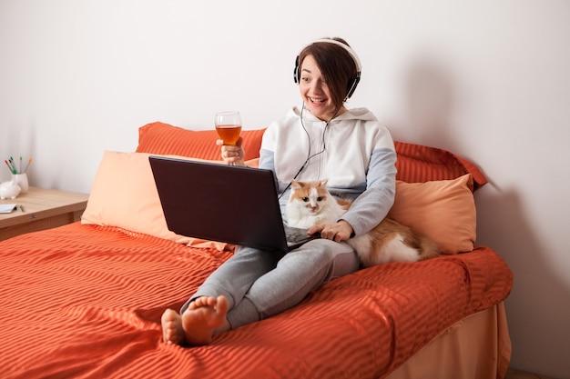Ein mädchen mit einem glas wein kommuniziert online mit freunden und verwandten, eine frau mit einem laptop auf dem bett und eine katze per videolink