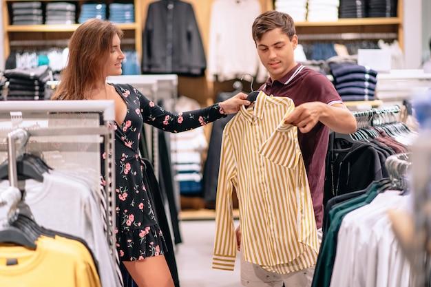 Ein mädchen mit einem mann geht zwischen den kleiderbügeln in einer boutique umher, wo ein mädchen bei der auswahl eines hemdes für einen mann hilft. einkaufen . auswahl der kleidung. schwarzer freitag. verkauf. große rabatte.