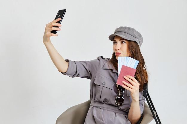 Ein mädchen mit einem pass, tickets macht selfie-fotos auf einem smartphone.