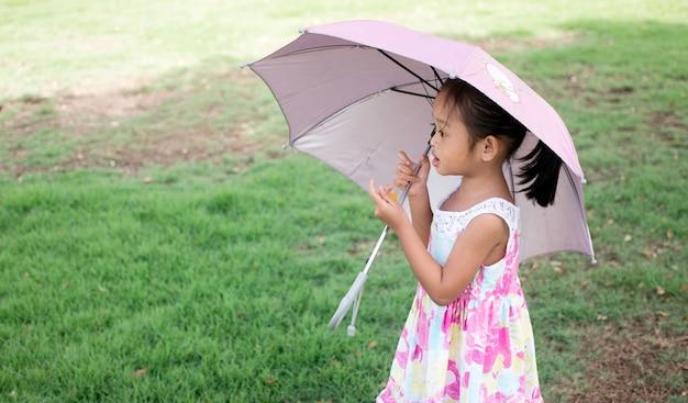 Ein mädchen mit einem rosa sonnenschirm im park.