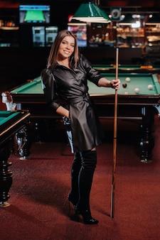 Ein mädchen mit einem stichwort in den händen steht in einem billardclub. russisches billard.