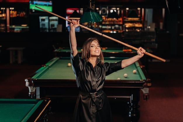 Ein mädchen mit einem stichwort in den händen steht in einem billardclub