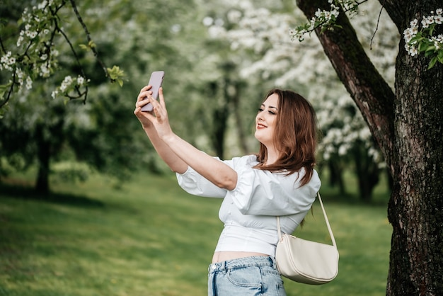 Ein mädchen mit einem telefon in der hand macht fotos von selfies, fotos für das internet Premium Fotos