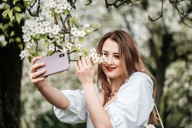 Ein mädchen mit einem telefon in der hand macht fotos von selfies, fotos für das internet