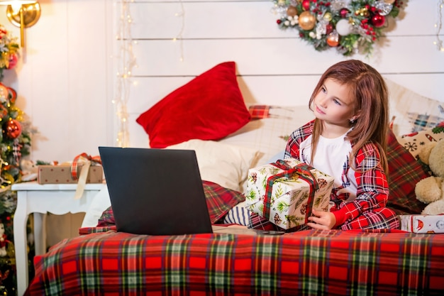 Ein mädchen mit einem weihnachtsgeschenk in den händen sitzt im schlafanzug auf einem bett gegenüber einem laptop in einem dekorierten schlafzimmer.
