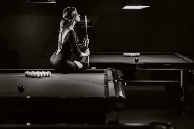 Ein mädchen mit einer augenbinde und einem queue in den händen sitzt auf einem tisch in einem billardclub. russisches billard. schwarz-weiß foto.