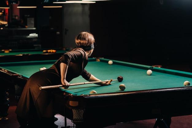 Ein mädchen mit einer augenbinde und einem stichwort in den händen in einem billardclub. russisches billard.