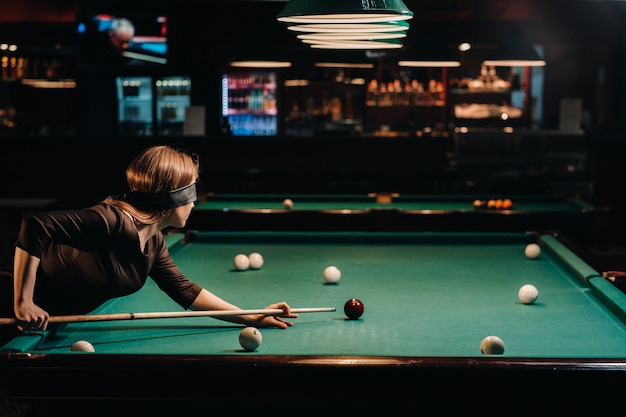 Ein mädchen mit einer augenbinde und einem stichwort in den händen in einem billardclub