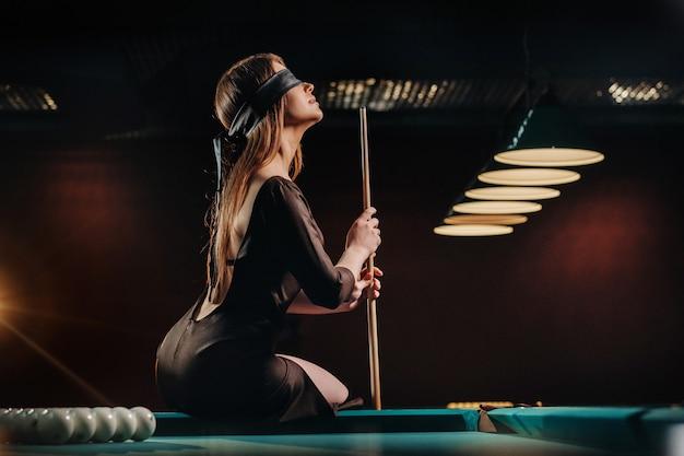 Ein mädchen mit einer augenbinde und einem stichwort in den händen sitzt auf einem tisch in einem billardclub. russisches billard.