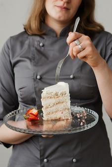 Ein mädchen mit einer gabel hält ein stück kuchen auf einem durchsichtigen tablett in den händen