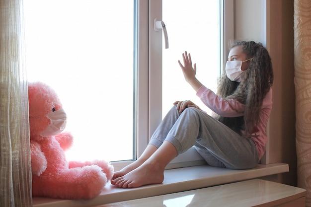 Ein mädchen mit einer gesichtsmaske im gesicht sitzt zu hause auf der fensterbank und berührt das fenster mit der hand. spielzeug rosa bär in einer gesichtsmaske.
