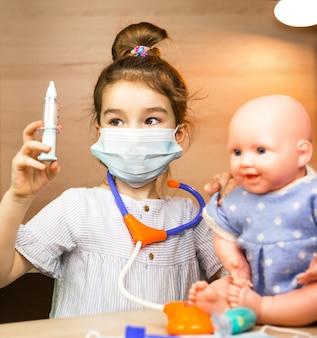 Ein mädchen mit einer puppe spielt arzt, macht eine spritzenimpfung in der hand. impfung, impfkalender, impfstoff, berufsspiel. krankenschwester injektion