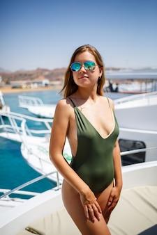 Ein mädchen mit einer schönen figur in einem grünen badeanzug. sie ist auf einer weißen yacht im roten meer