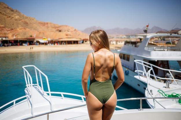 Ein mädchen mit einer schönen figur in einer grünen bademode. sie ist auf einer weißen yacht im roten meer