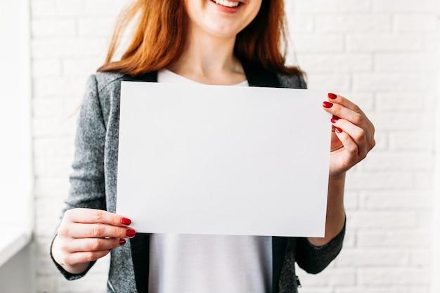 Ein mädchen mit europäischem aussehen hält ein weißes blatt papier für die platzierung einer inschrift, einer werbung, eines slogans, einer marke