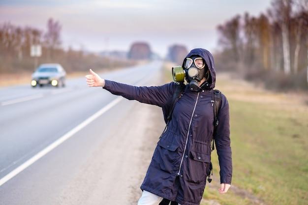 Ein mädchen mit gasmaske auf der straße hebt die hand und bittet darum, keine autos vorbeifahren zu lassen