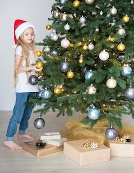 Ein mädchen mit geschenken spielt in der nähe des weihnachtsbaums. wohnzimmerinnenraum mit weihnachtsbaum und dekorationen. neujahr. geschenk geben.