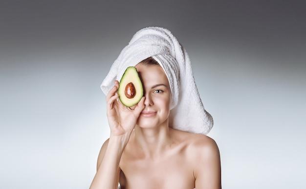 Ein mädchen mit gesunder und schöner haut hält eine avocado nahe ihrem gesicht