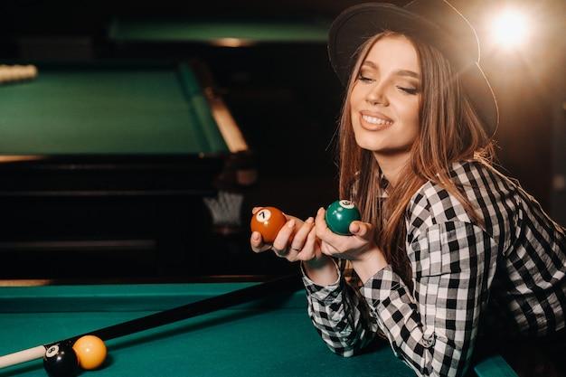 Ein mädchen mit hut in einem billardclub mit bällen in den händen. billard spielen