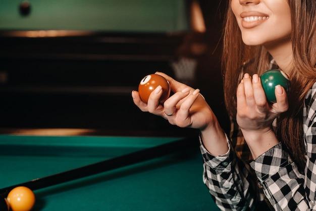 Ein mädchen mit hut in einem billardclub mit bällen in den händen