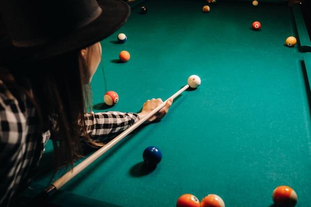 Ein mädchen mit hut in einem billardclub mit einem queue in den händen schlägt einen ball