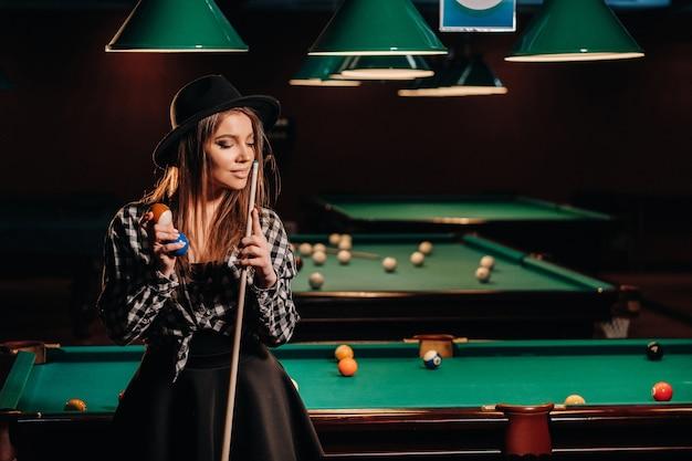 Ein mädchen mit hut in einem billardclub mit einem queue in ihren händen. billard-spiel.