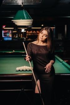 Ein mädchen mit hut in einem billardclub mit einem queue in ihren händen.pool-spiel.