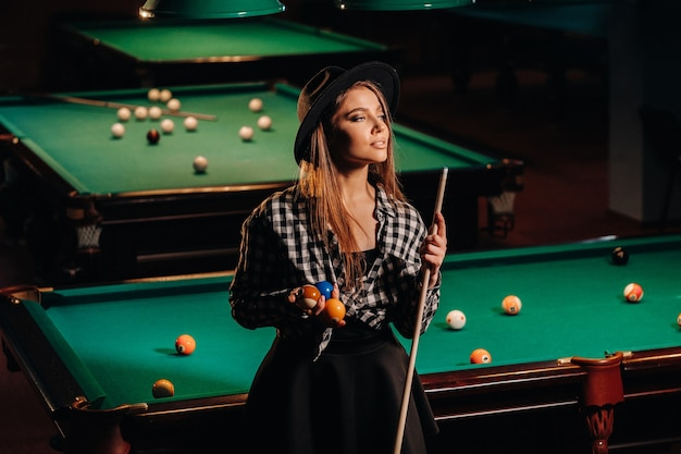 Ein mädchen mit hut in einem billardclub mit einem stichwort in den händen. billardspiel.