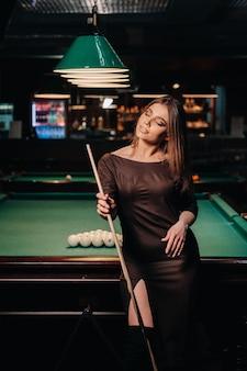 Ein mädchen mit hut in einem billardclub mit einem stichwort in den händen. poolspiel.