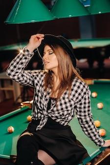 Ein mädchen mit hut in einem billardclub sitzt auf einem billardtisch. billard spielen.