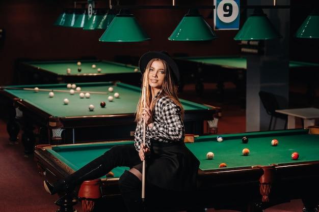 Ein mädchen mit hut in einem billardclub sitzt auf einem billardtisch mit einem queue in den händen. billard spielen