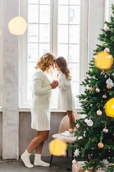 Ein mädchen mit ihrer mutter in der nähe des weihnachtsbaumes, das interieur dekoriert für das neue jahr und weihnachten, familie und freude, traditionen