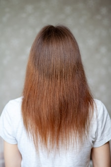 Ein mädchen mit langen, glatten und schönen braunen haaren. haarpflege zu hause.